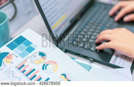 Sale Report And Business Financial Graph Chart On Blur Office Worker Hand Typing On The Laptop At Th