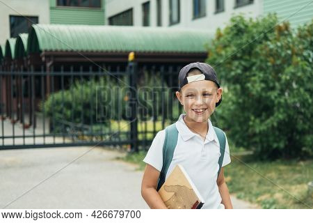 Smiling Boy, Elementary School Student, Walking To School With Bag Behind Back And Book. Students Ar