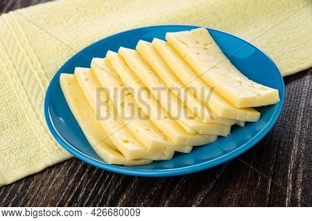 Yellow Napkin, Slices Of Cheese In Blue Glass Saucer On Dark Wooden Table
