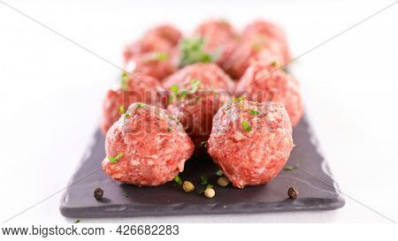 raw meatballs with parsley on white background