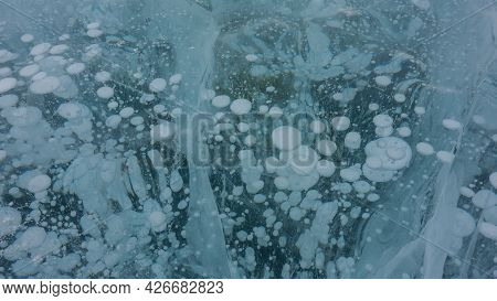Turquoise Ice Surface. Close-up. Full Frame. Crossing Cracks, Bubbles Of Frozen Methane Gas Are Visi