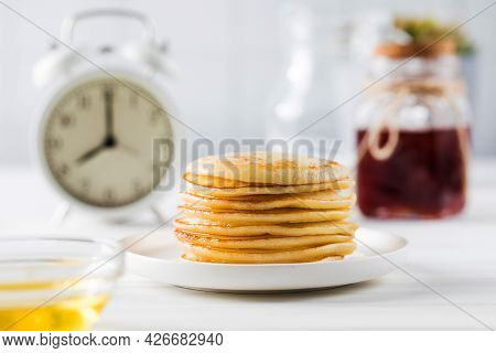 The Pancakes Are Stacked In A Plate. In The Background, Berry Sauce And An Alarm Clock. Breakfast Co