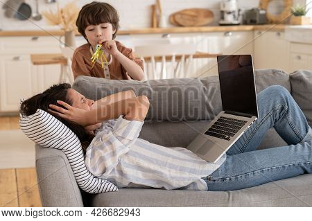 Overwhelmed Young Mother Covering Ears And Screaming Annoyed With Little Son Bad Behavior. Millennia