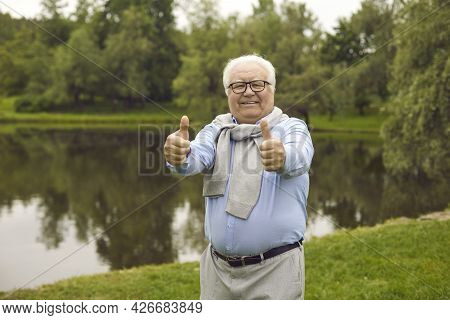 Portrait Of A Happy Senior Citizen Standing In A Green Park And Giving A Thumbs Up