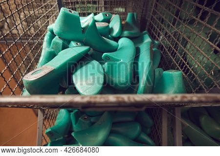 Pile Of Plastic Shoe Lasts In Container In Warehouse At Footwear Manufacturing Factory