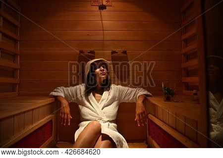 Young Woman Relaxing In The Infrared Sauna During A Procedure At The Spa Resort Center. Body Care