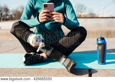 Young sportswoman with prosthesis holding mobile phone while sitting on a fitness mat outdoors cropped