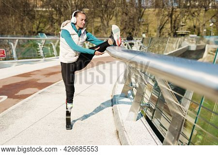 Warming up before run. Side view of disabled positive woman in sportswear and headphones stretching prosthetic leg while standing on the bridge