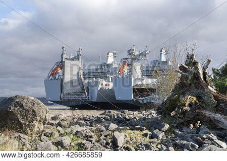 Two Battleships Parked Near The Rocky Shoreline In Tacoma, Washington