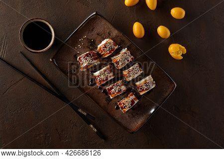 Sushi Rolls With Eel, Cream Cheese, Kumquats And Unagi Sauce