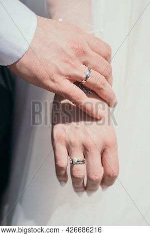 Close-up Of The Ring Newlyweds. The Groom Gently Touches The Brides Hand. Husband And Wife Hold Hand