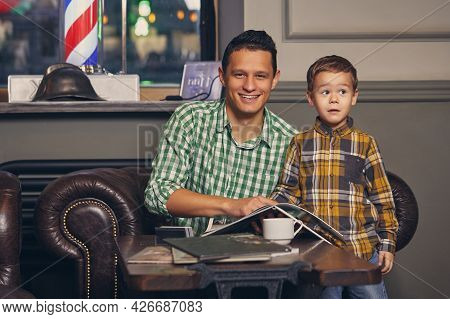 Young Father And His Stylish Little Son In The Barbershop In The Waiting Room.