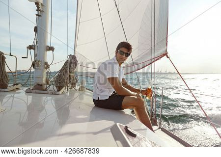 Confident young man sitting and drinking beer on his yacht in sea or ocean. Luxury boat. Beautiful guy wear shorts, shirt and glasses. Concept of sailing vacation or tourism. Summertime. Sunny daytime