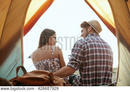 View from tent on young european couple rest on beach. Guy embracing his girlfriend. Pleased guy and girl. Concept of romantic relationship and enjoying time together. Camping vacation at summertime