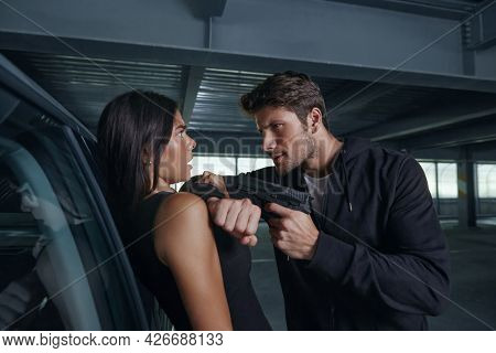 Aggressive robber threatening with pistol to frightened girl. European man and young brunette woman stand near auto. Male bandit wear hoodie. Concept of robbery and kidnapping. Inside parking lot