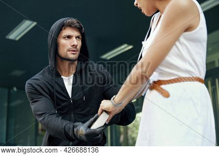 Aggressive robber want to steal handbag of frightened girl. European male bandit wear black hoodie and gloves. Woman wear white dress. Concept of robbery. City daytime
