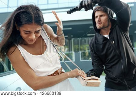 Aggressive robber want to steal handbag of frightened girl. Man threatening with pistol to young european brunette woman. Male bandit wear black hoodie. Concept of robbery. City daytime