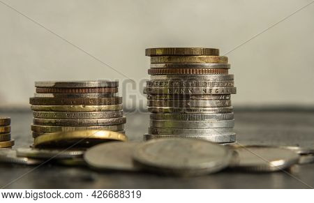Two Stacks Of Different Coins On The Background Of A Pile Of Other Coins. Selective Focus. The Conce