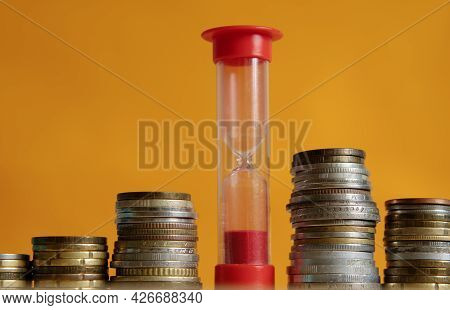 Red Hourglass And Stacks Of Coins On An Orange Background. The Concept Of Time And Money. Close-up