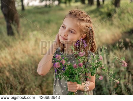 Beautiful preteen girl with incredible eyes looking back and holding flower bouquet on the nature. Portrait of cute female kid with hairstyle in the field in summer time with blurred background