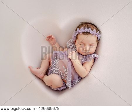 Adorable newborn baby girl wearing beautiful dress and wreath lying in heart shape decoration and sleeping in studio. Cute infant child napping
