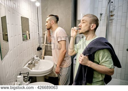 Young men brushing teeth in front of mirrors in dorm bathroom in the morning
