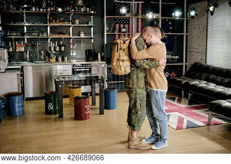 Young upset gay man seeing off his boyfriend to army in the kitchen of their apartment