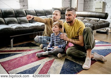 Amazed preteen boy and two guys sitting on the floor and playing new videogame at home