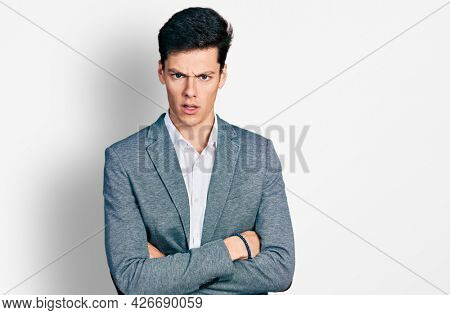 Young hispanic business man with arms crossed gesture in shock face, looking skeptical and sarcastic, surprised with open mouth