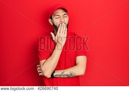 Hispanic man with beard wearing delivery uniform and cap bored yawning tired covering mouth with hand. restless and sleepiness.