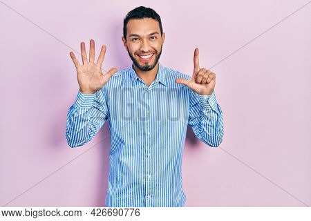 Hispanic man with beard wearing casual blue shirt showing and pointing up with fingers number seven while smiling confident and happy.