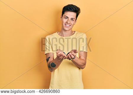 Young hispanic man wearing casual yellow t shirt smiling with hands palms together receiving or giving gesture. hold and protection
