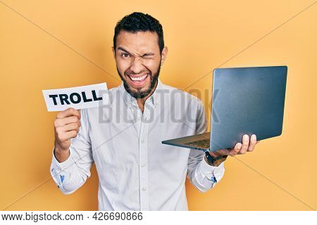 Hispanic man with beard working using computer laptop holding banner with troll word winking looking at the camera with sexy expression, cheerful and happy face.