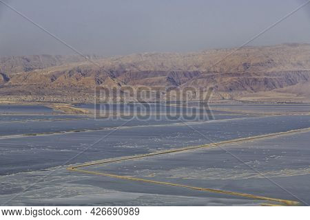 View Of The Jordanian Mountains Through The Saline Waters Of The Dead Sea At Sunset