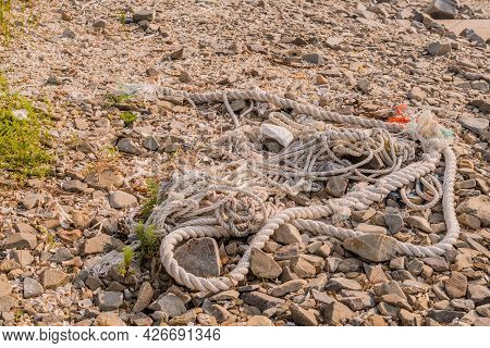 Strand Of Used Discarded Rope Laying On Rocky Ground.