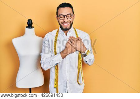 Hispanic man with beard dressmaker designer standing by manikin smiling with hands on chest with closed eyes and grateful gesture on face. health concept.