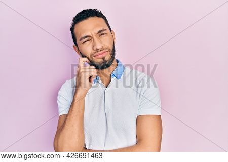 Hispanic man with beard wearing casual white t shirt thinking concentrated about doubt with finger on chin and looking up wondering