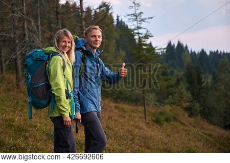 Two Young Tourists With Joyful Facial Expressions Holding Hands While Walking Outdoors. Man Pleased