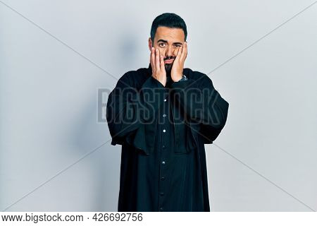 Handsome hispanic man with beard wearing catholic priest robe tired hands covering face, depression and sadness, upset and irritated for problem