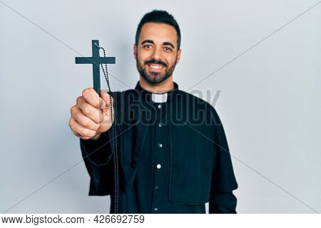 Handsome hispanic priest man with beard holding catholic cross looking positive and happy standing and smiling with a confident smile showing teeth