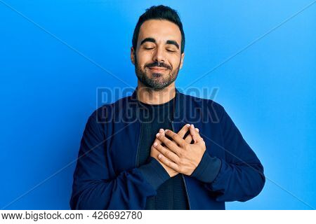Young hispanic man wearing casual clothes smiling with hands on chest, eyes closed with grateful gesture on face. health concept.