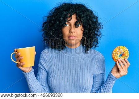 Young hispanic woman eating doughnut and drinking coffee relaxed with serious expression on face. simple and natural looking at the camera.