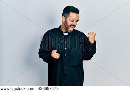 Handsome hispanic man with beard wearing catholic priest robe celebrating surprised and amazed for success with arms raised and eyes closed. winner concept.