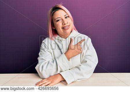 Hispanic woman with pink hair wearing casual sweatshirt sitting on the table cheerful with a smile of face pointing with hand and finger up to the side with happy and natural expression on face