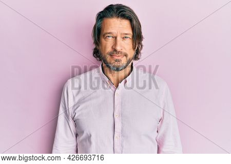 Middle age handsome man wearing business shirt with serious expression on face. simple and natural looking at the camera.