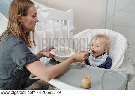 Serious young Caucasian mother sitting in front of baby and feeding him with spoon, she giving him to porridge