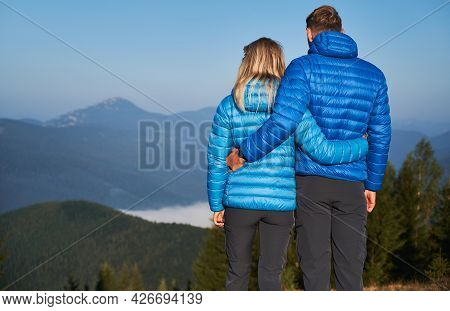 Rear View Of Couple Hikers Holding Each Other Around Waist And Contemplating On Fabulous Mountain La