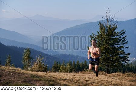 Shirtless Young Man Running Up Grassy Hill With Blue Sky And Mountains On Background. Muscular Trail