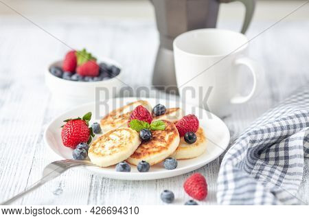 Cottage Cheese Pancakes With Fresh Berries, Cup Of Coffee And Coffee Maker On White Wooden Table. Ta