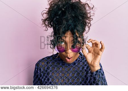 Young hispanic woman wearing cool sunglasses scared and amazed with open mouth for surprise, disbelief face